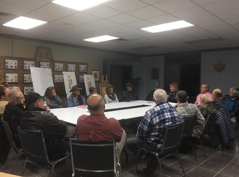 Des gens assis autour d'une table assistent à une réunion.