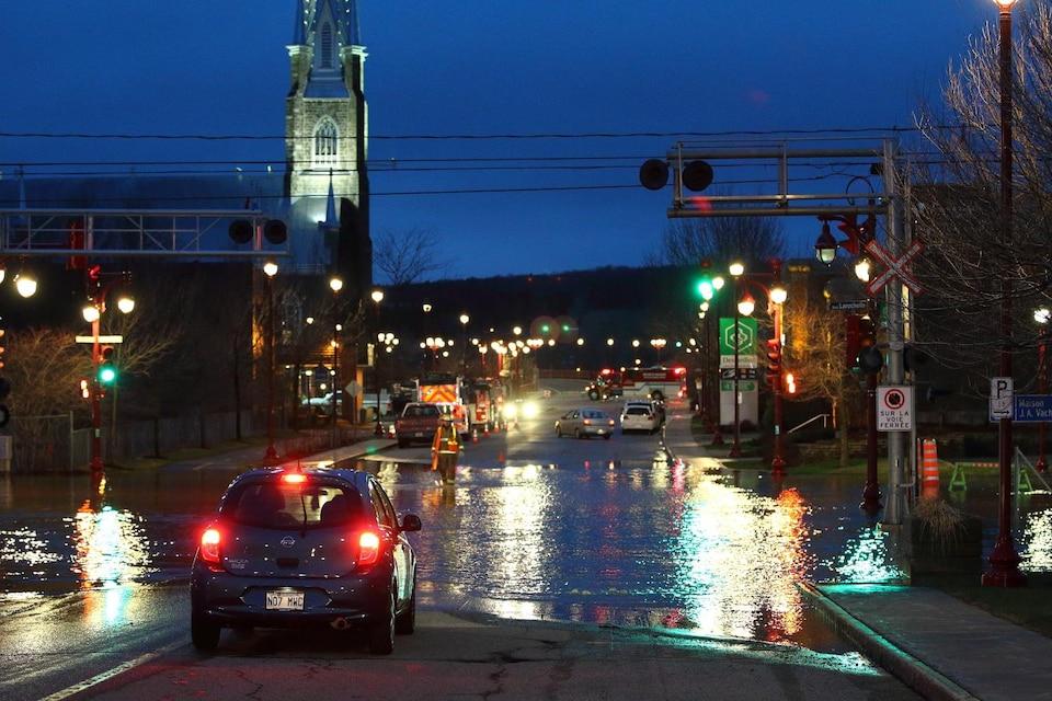 Une voiture circule sur une rue inondée au centre-ville de Sainte-Marie, en Beauce. La photographie a été prise de soir.