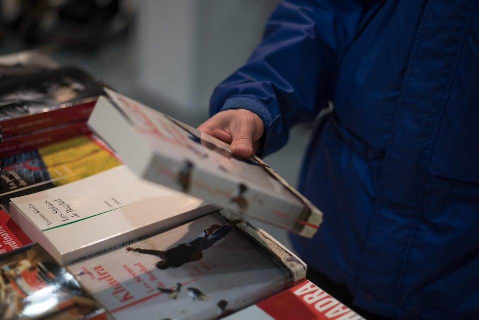 Une personne tient un livre dans sa main lors du Salon du livre de Québec.