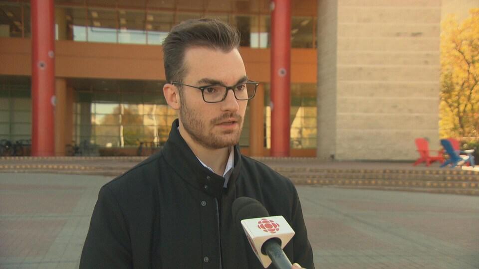 Un jeune homme répond aux questions d'un journaliste devant l'hôtel de ville d'Ottawa.