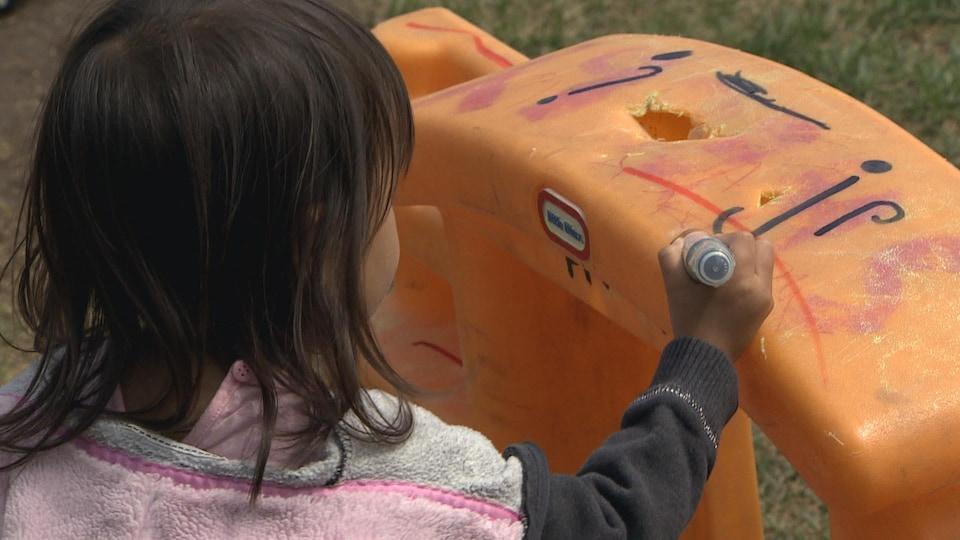 Une petite fille aux cheveux noirs dessine avec un crayon-feutre sur une structure en plastique orange.