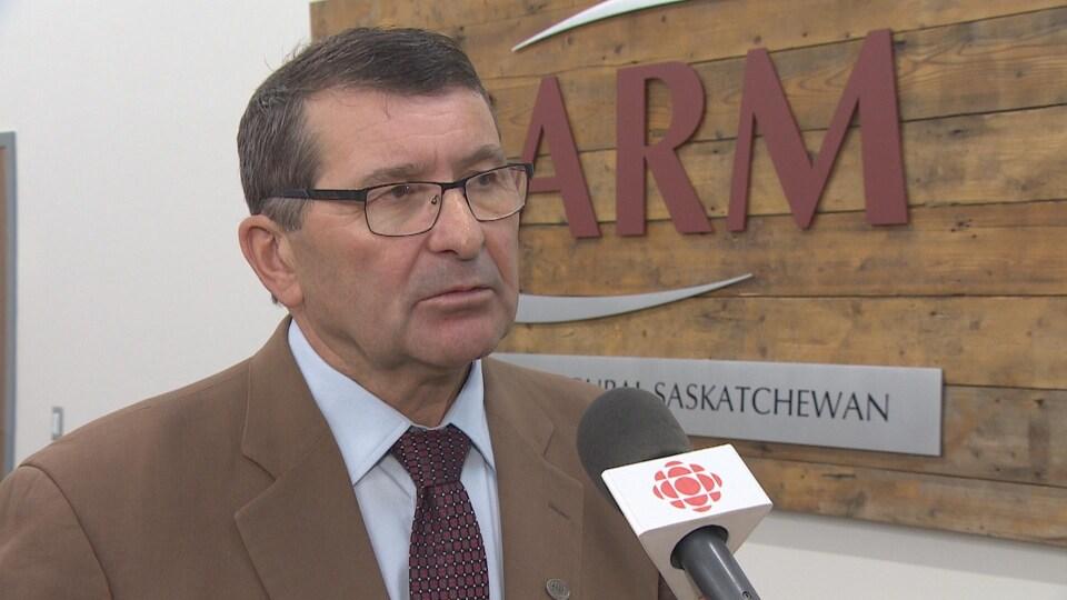 Ray Orb parle à la caméra devant l'affiche de l'Association Association des municipalités rurales de la Saskatchewan.