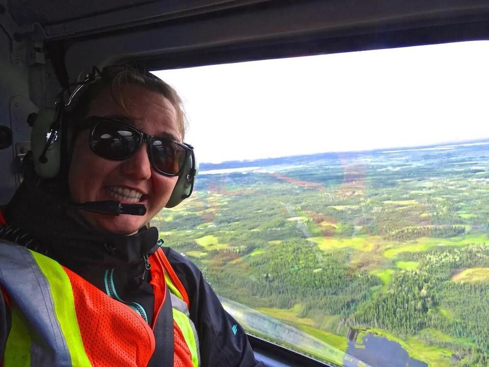 Portrait de la chercheuse Carolyn Gibson depuis les airs, au-dessus d'une région boisée de la région de Fort Simpson, T.N.O.