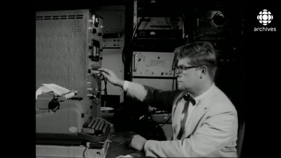 Homme bien mis et bien vêtu en veston avec noeud papillon devant une machine à écrire tout en manipulant des câbles sur un moniteur