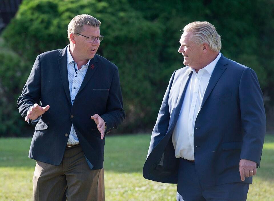 Scott Moe parle à Doug Ford dans un parc.