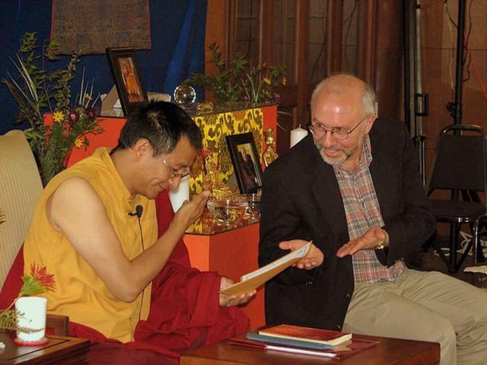 Scott Wellenbach devant un moine bouddhiste qui consulte un texte.