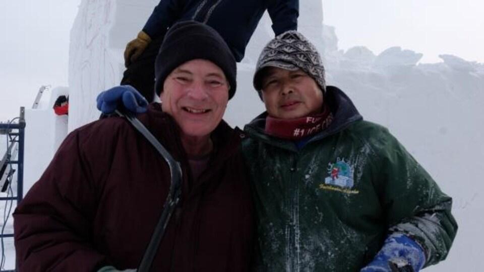 Deux hommes qui portent des manteaux d'hiver et des tuques sourient pour la caméra dans un décor hivernal.