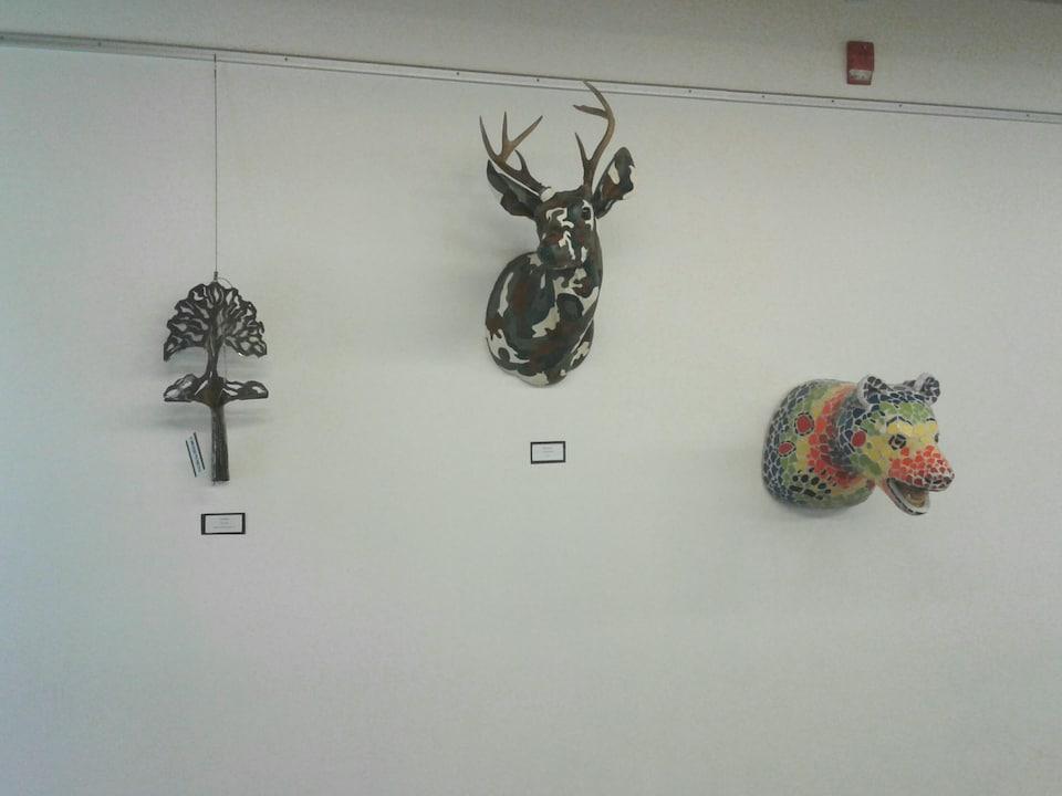 Trois oeuvres d'arts accrochés au mur : une pelle transformée en arbre, un cerf camouflé et un ours coloré.