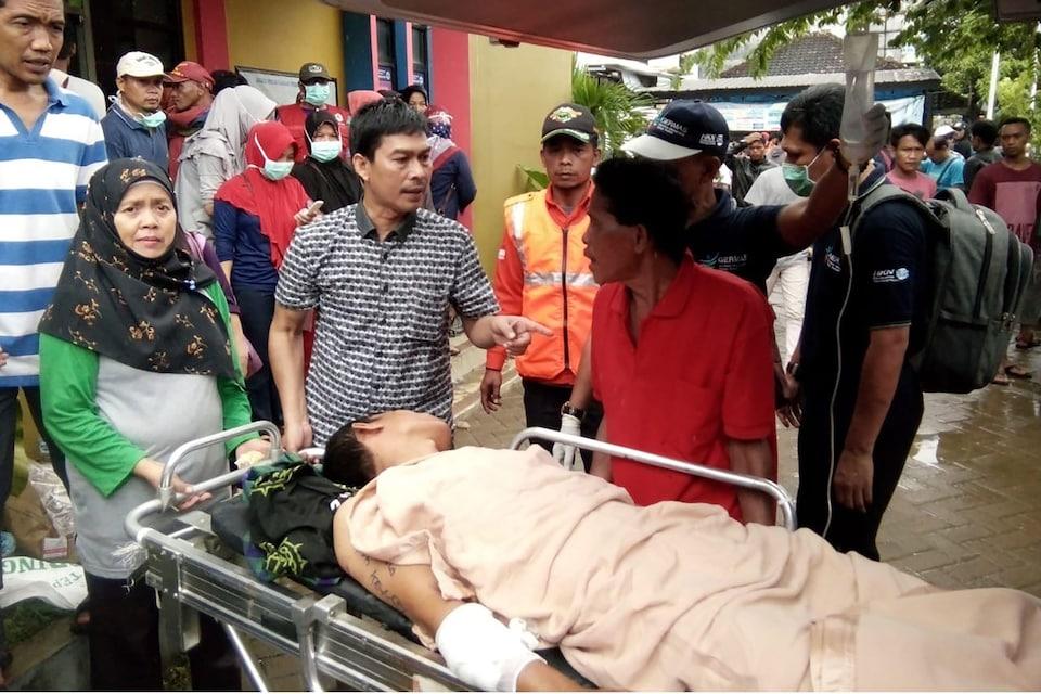 Une personne est couchée sur une civière et reçoit des soins.