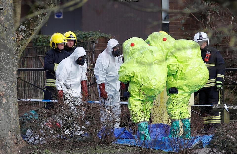 Des agents de la police en combinaisons protectrices jaune et blanche s'affairent sur la scène de crime.