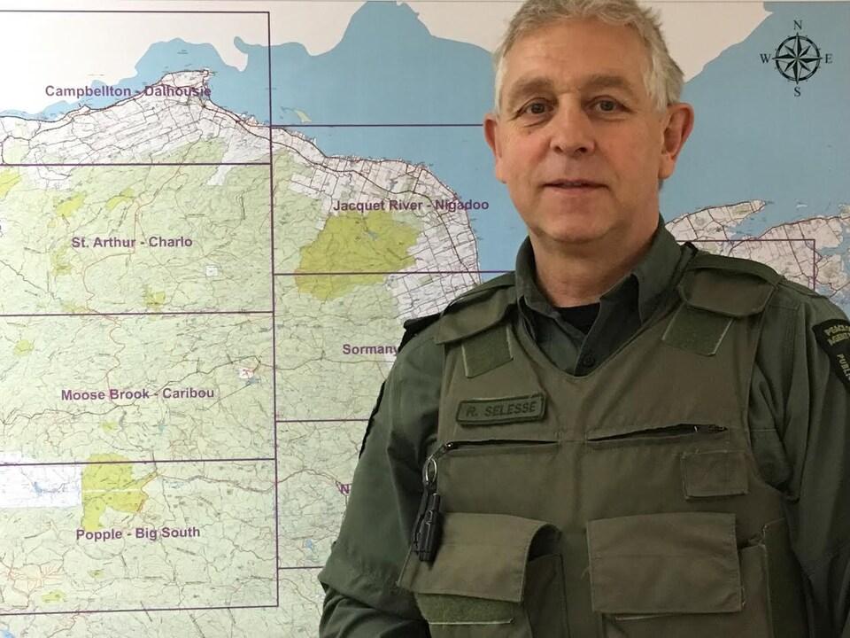 Roger Selesse devant une carte géographique du nord du Nouveau-Brunswick