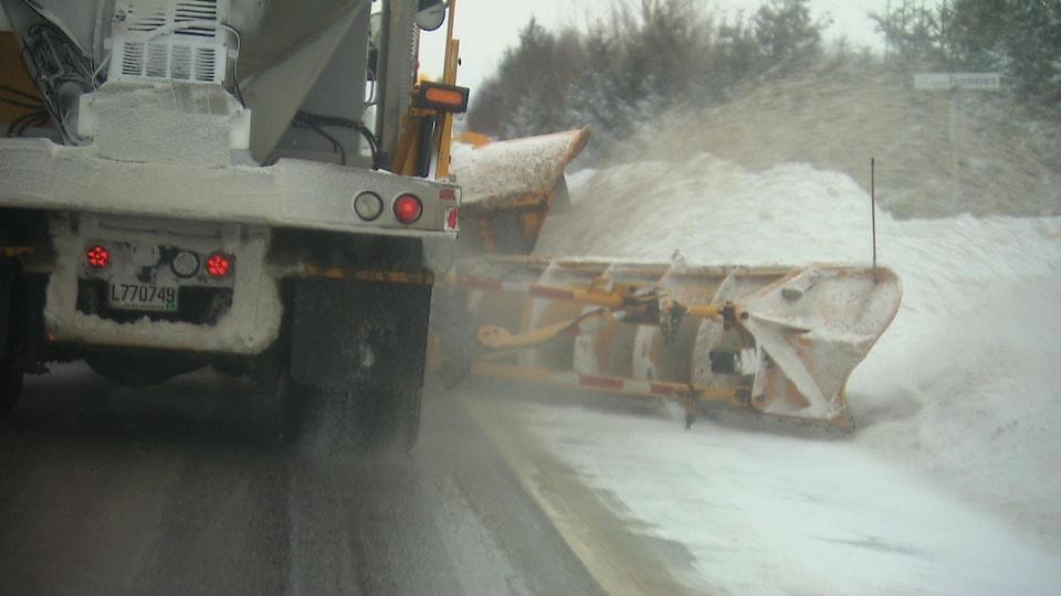 Arrière d'une déneigeuse qui épand du sel et qui pousse la neige sur le bord de la route.