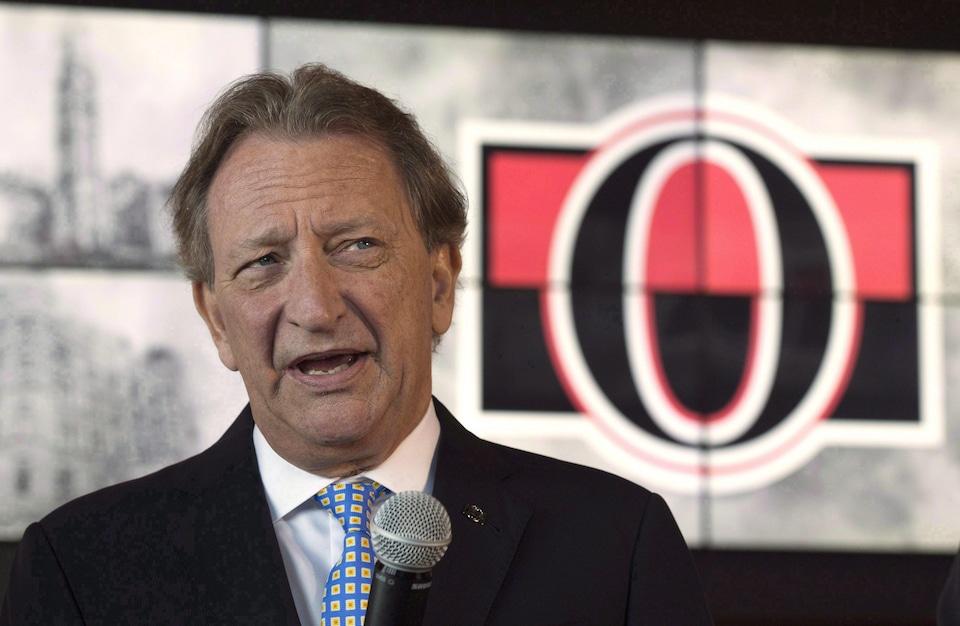 M. Melnyk parle à un micro devant un logo des Sénateurs d'Ottawa.