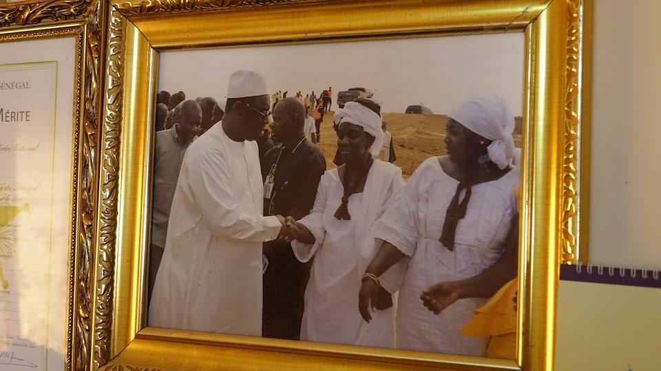 Une photographie qui se trouve dans un cadre dont les côtés ont des fioritures est prise en photo. Sur la photographie, une femme et un homme se serrent la main.
