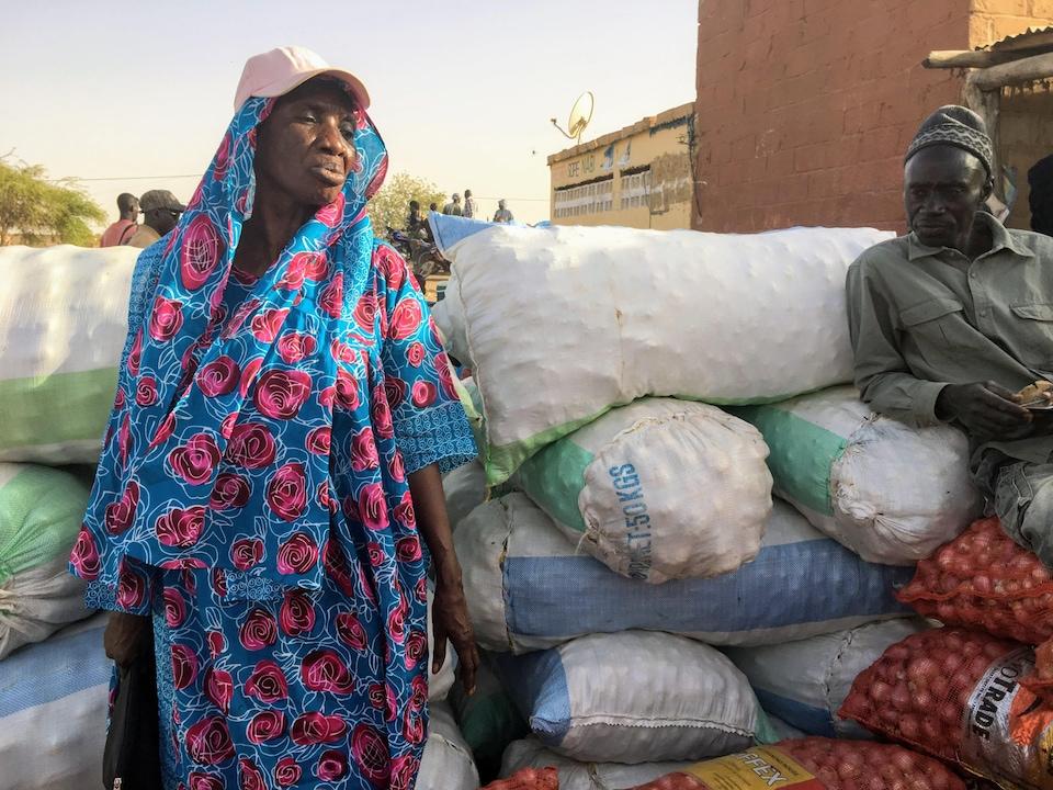Une femme portant une robe fleurie et une casquette se tient près de nombreux sacs. Ces derniers semblent contenir des légumes.