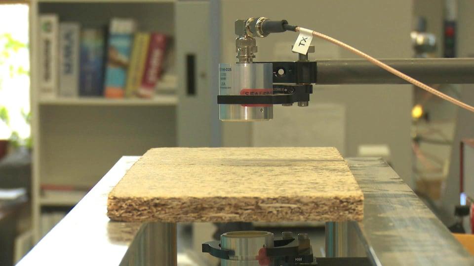 Une machine scanne un panneau de particules