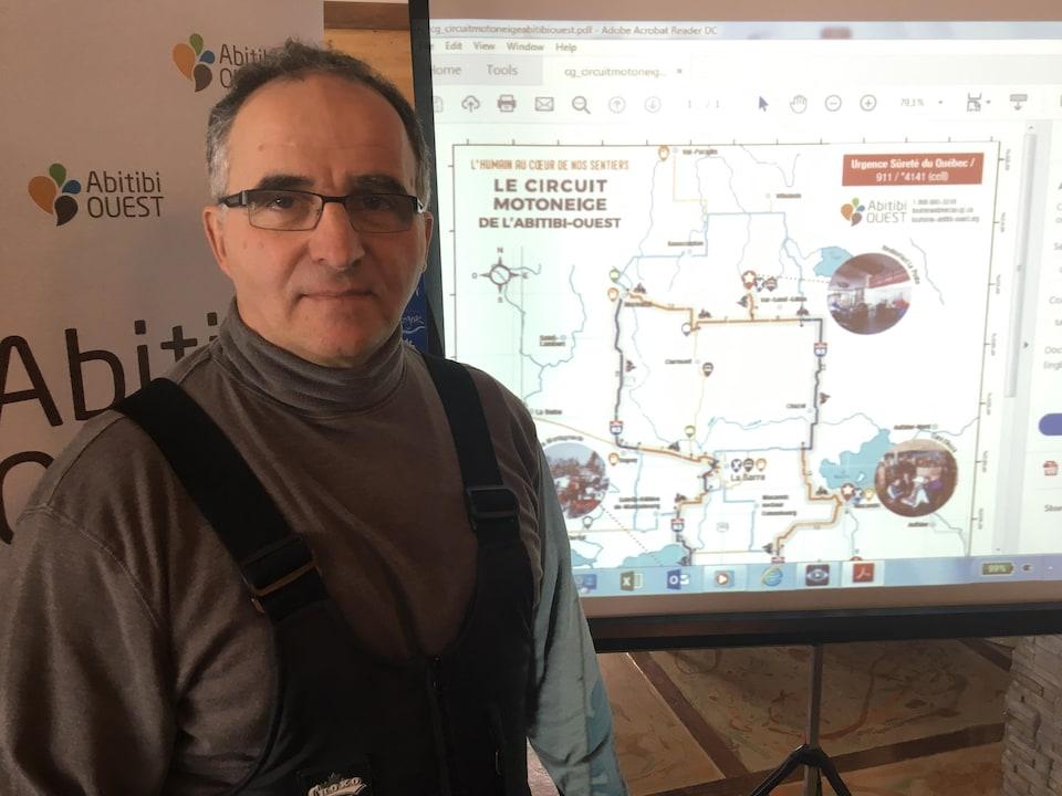 Un homme pose pour la caméra devant une carte montrant un nouveau circuit de motoneige.