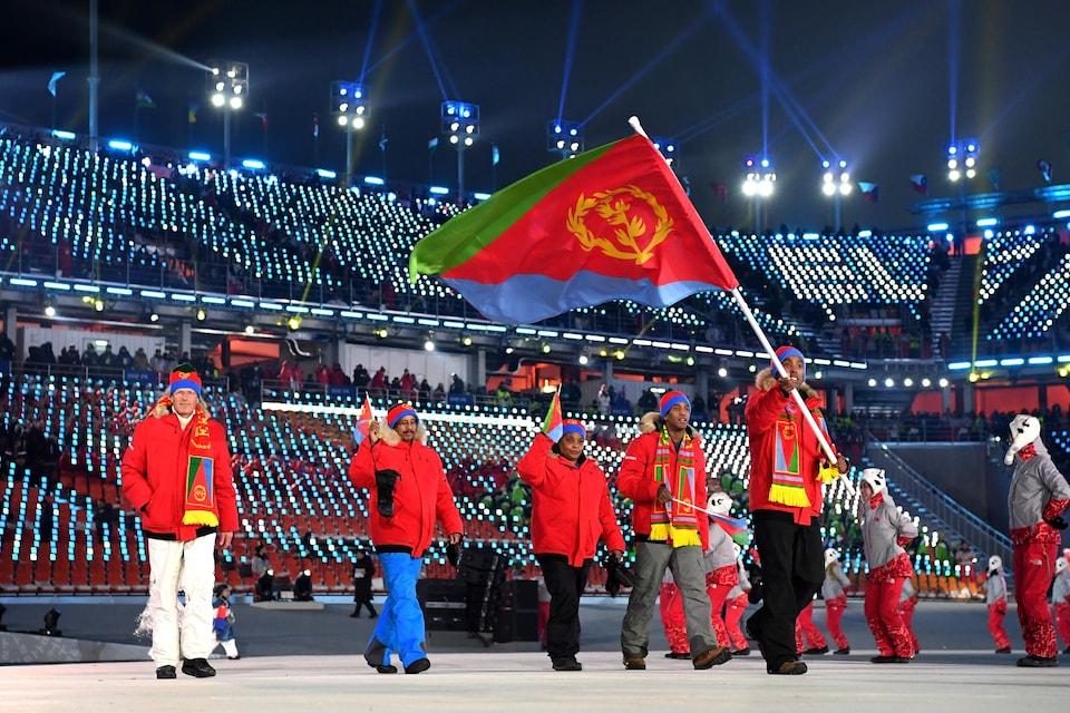 Pyeongchang, 9 février 2018. Shannon-Ogbani Abeda porte le drapeau de l'Érythrée lors de la cérémonie d'ouverture des Jeux olympiques de Pyeongchang. Il marche dans le stade suivi de 4 accompagnateurs de sa délégation.   (Photo de Matthias Hangst/Getty Images)