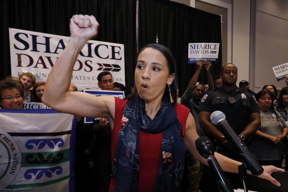 Sharice Davids lève le poing en l'air en s'adressant à ses partisans.