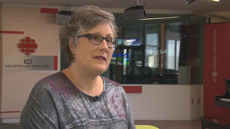 Sharon Hatcher devant le logo de Radio-Canada en entrevue.