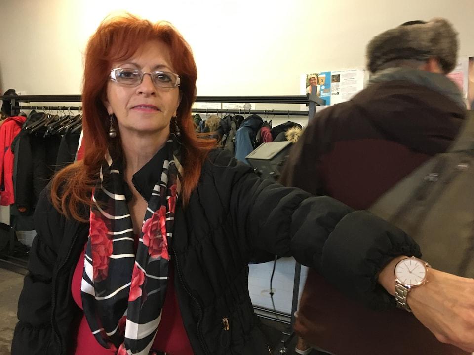 Une dame pose fièrement avec sa montre réparée.