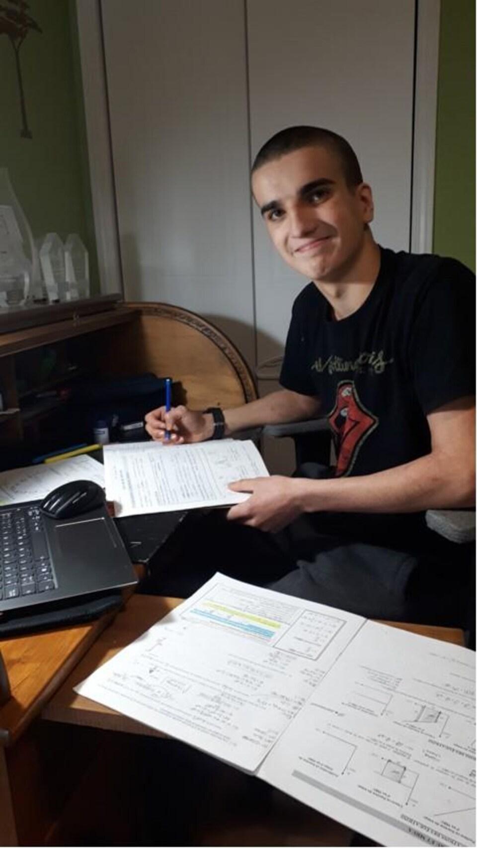 Le jeune homme est devant l'ordi avec ses devoirs.