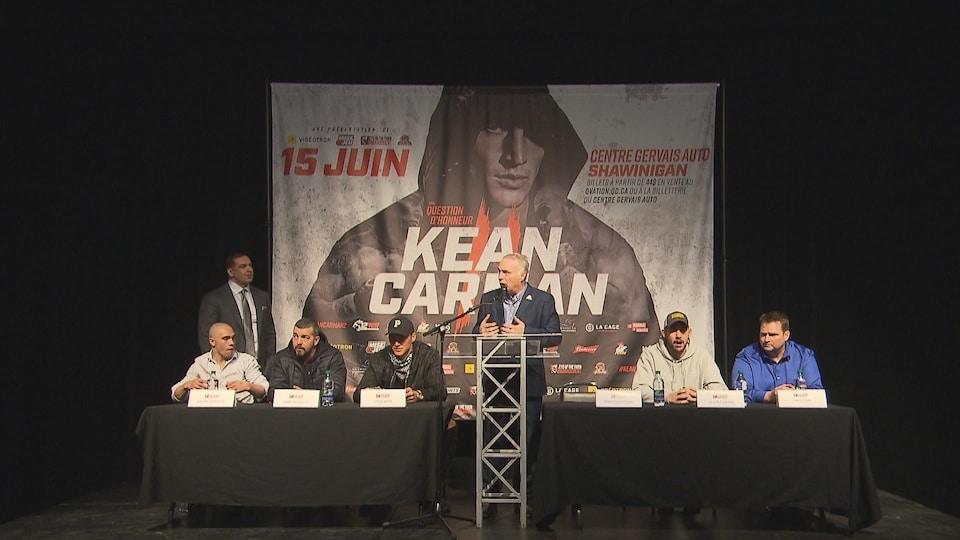 Gens assis devant une affiche du combat, lors d'une conférence de presse