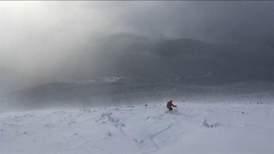 Un skieur descend en skis dans le parc de la Gaspésie