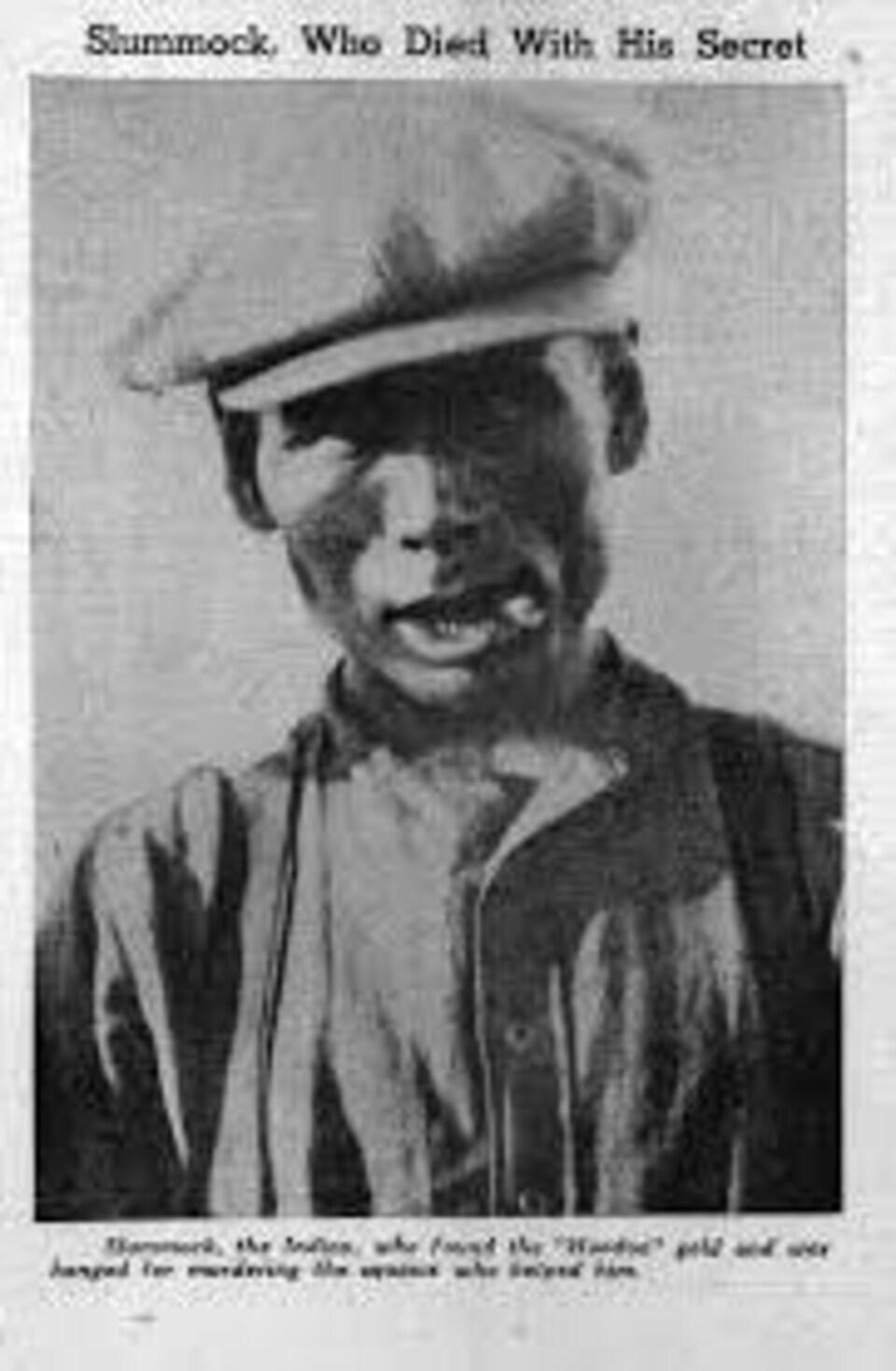 Photo en noir et blanc d'un homme, mégot de cigarette à la bouche.