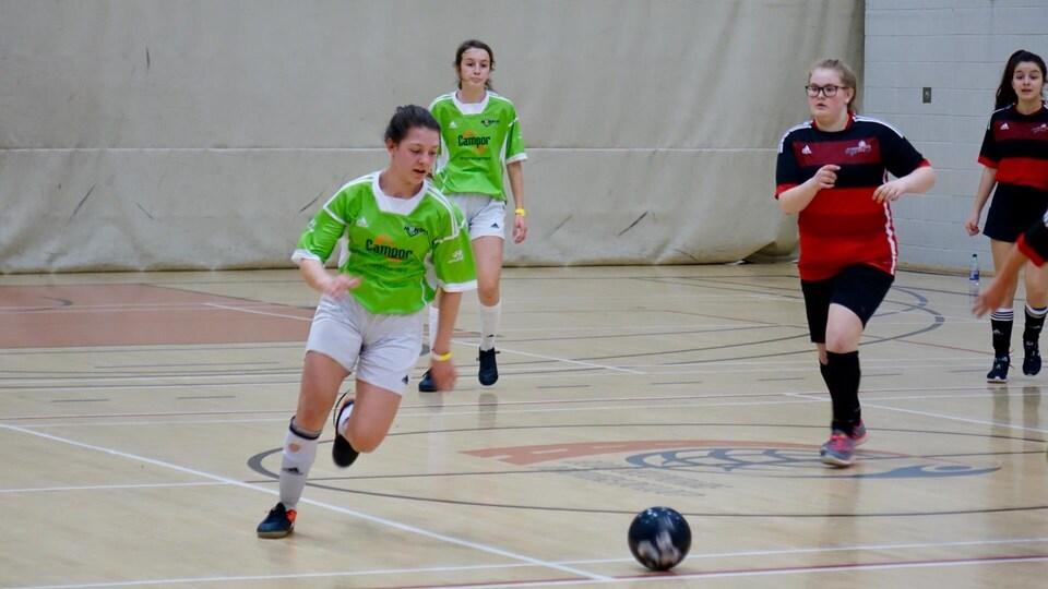 Des jeunes filles jouent au soccer dans un stade intérieur.