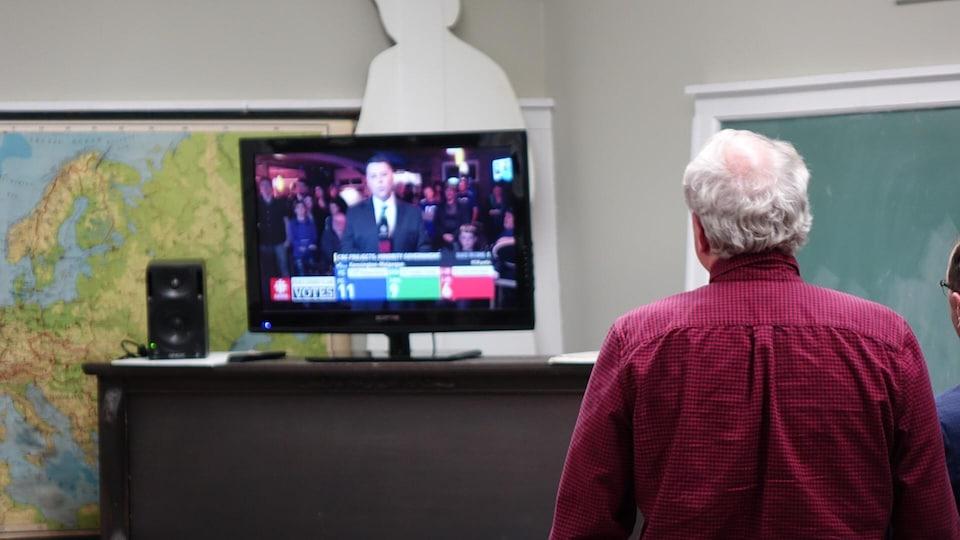 Le chef du Parti libéral écoute une entrevue à la télévision, lors de la soirée électorale.