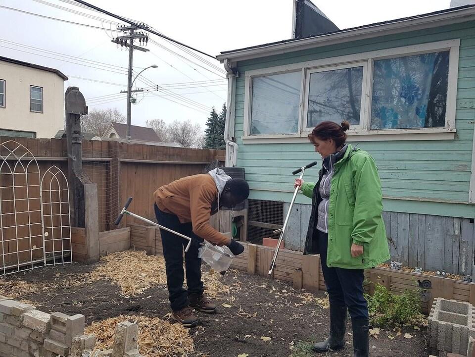 Une femme et un homme amassent des échantillons de terre dans un jardin.