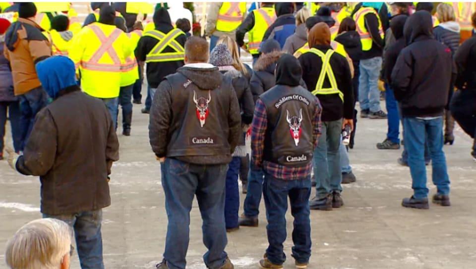 Deux hommes sont vus de dos parmi les manifestants. Ils portent des vestes à l'effigie des Soldats d'Odin du Canada.