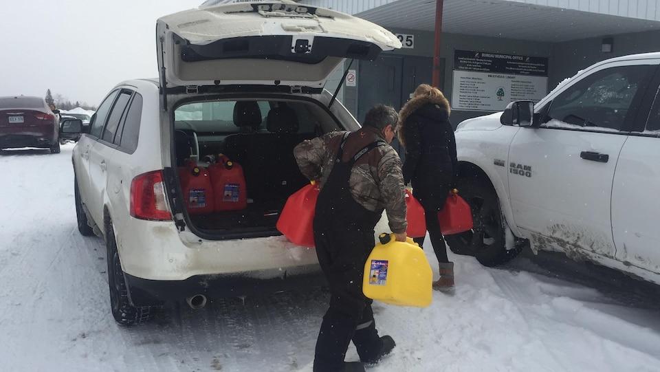 Des gens transportent des bidons d'essence.