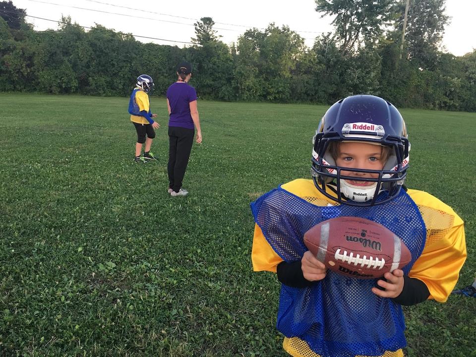 Un jeune garçon dans son uniforme avec un ballon de football dans les mains avec son entraîneuse en arrière-plan