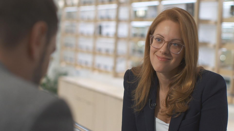 La jeune femme est assise devant un étalage de lunettes.