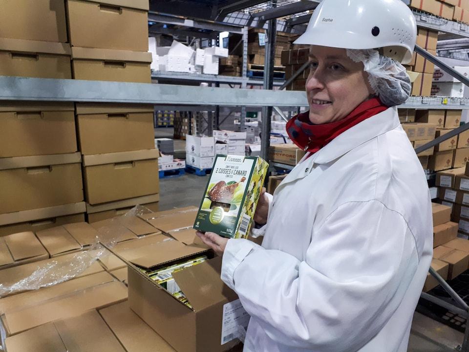 Sophie Desforges, responsable recherche et développement chez Gibiers Canabec, tient une boite de cuisses de canard confites dans l'entrepôt de l'entreprise à Saint-Augustin-de-Desmaures