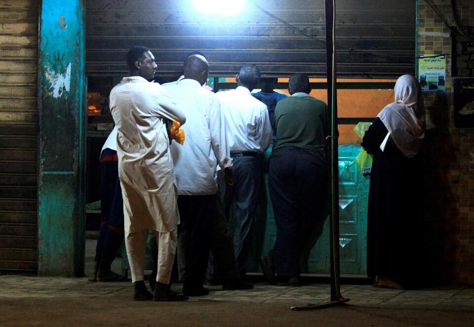 Des Soudanais faisant la file devant une boulangerie à Khartoum. Le pays connaît une pénurie de pain, dont le prix a triplé depuis quelques semaines.