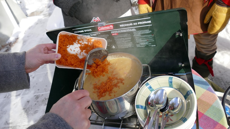 Dans le chaudron, on ajoute les carottes râpées à la soupe aux pois.