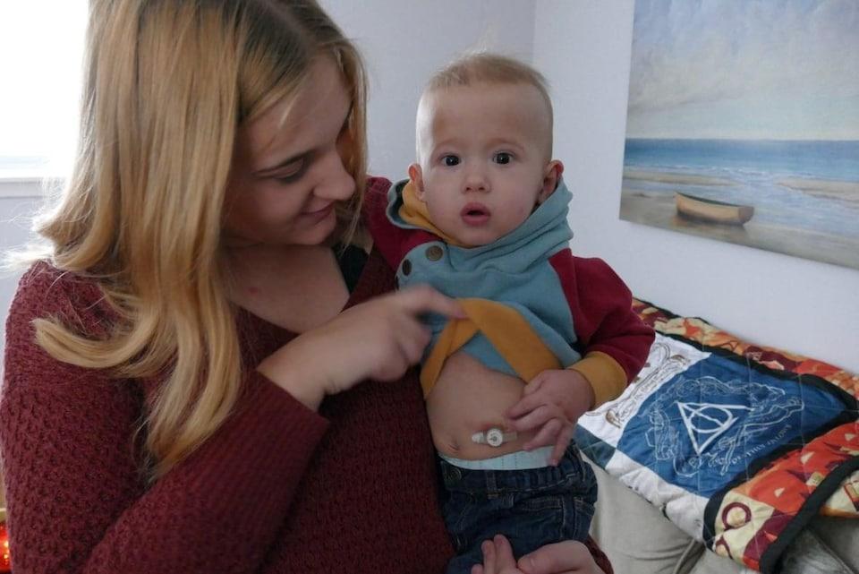 Une femme debout dans un salon tenant dans les bras un petit garçon.