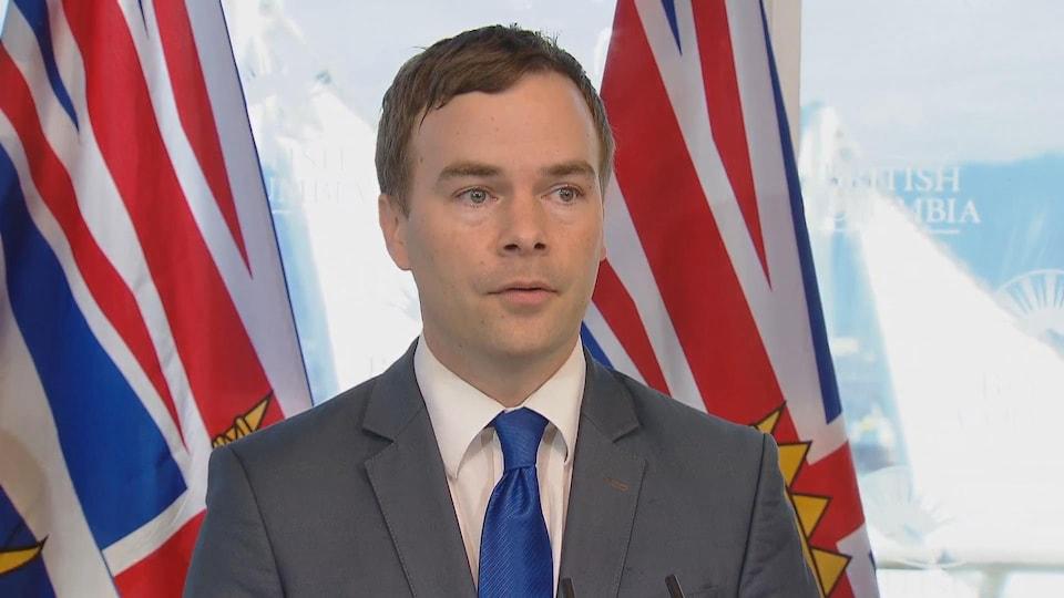 Un homme avec une cravate bleue devant des drapeaux de la Colombie-Britannique.