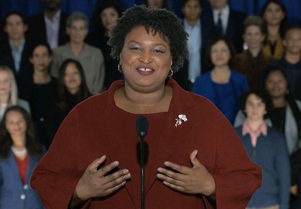 La démocrate Stacey Abrams, parlant à la caméra, devant des partisans