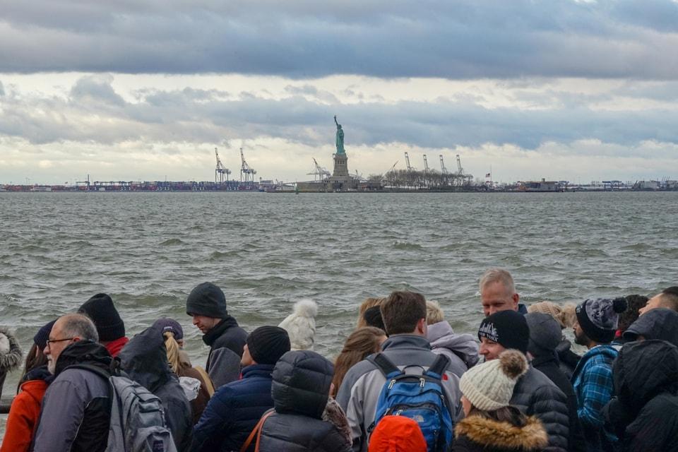 Des touristes attendent le traversier pour se rendre à la statue de la Liberté, que l'on voit au loin.