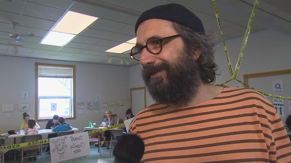 Il porte une barbe et un chapeau.