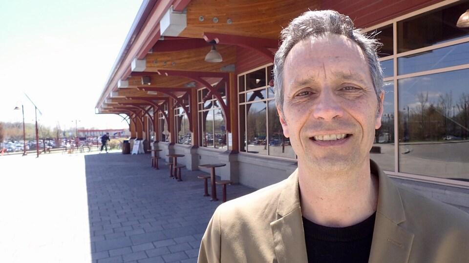 Le maire de Saint-Jérôme, Stéphane Maher, pose devant la gare intermodale de sa ville.