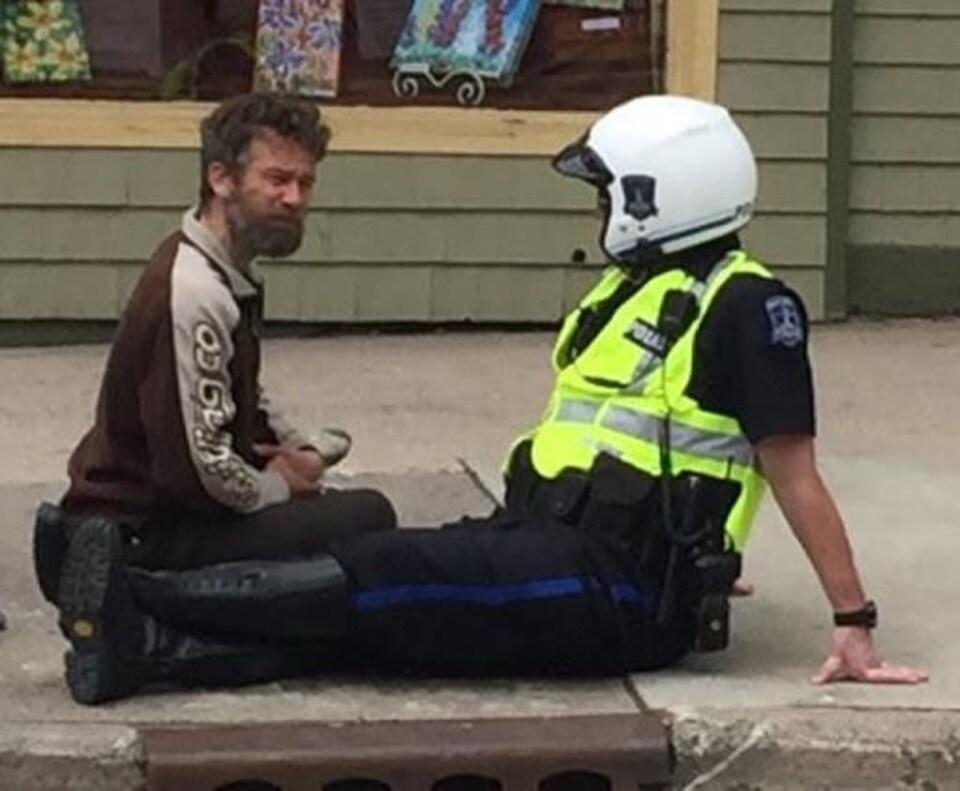 Un itinerant et une policière discutent ensemble de façon agréable.