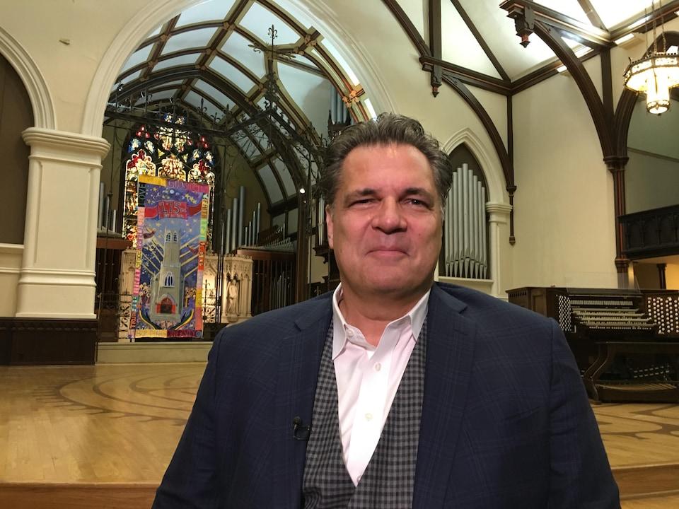 Stephen Mansfield pose, tout sourire, dans une église.