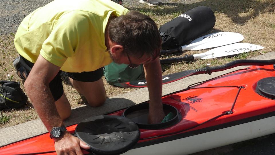 Un homme est penché par dessus un kayak, qui est immobilisé sur le gazon. La main gauche de l'homme touche la partie avant du kayak. On voit des rames à côté du kayak.