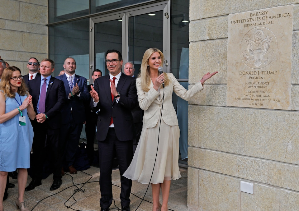 Le secrétaire au Trésor Steve Mnuchin applaudit aux côtés d'Ivanka Trump, qui montre la plaque sur laquelle on peut lire le nom de son père.