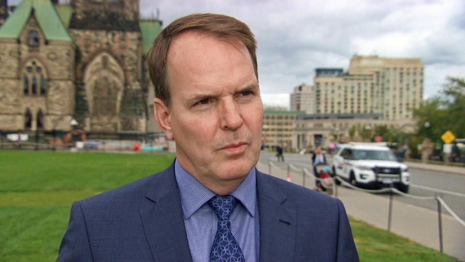 Steven MacKinnon en entrevue sur la colline du Parlement, à l'extérieur, devant la pelouse.